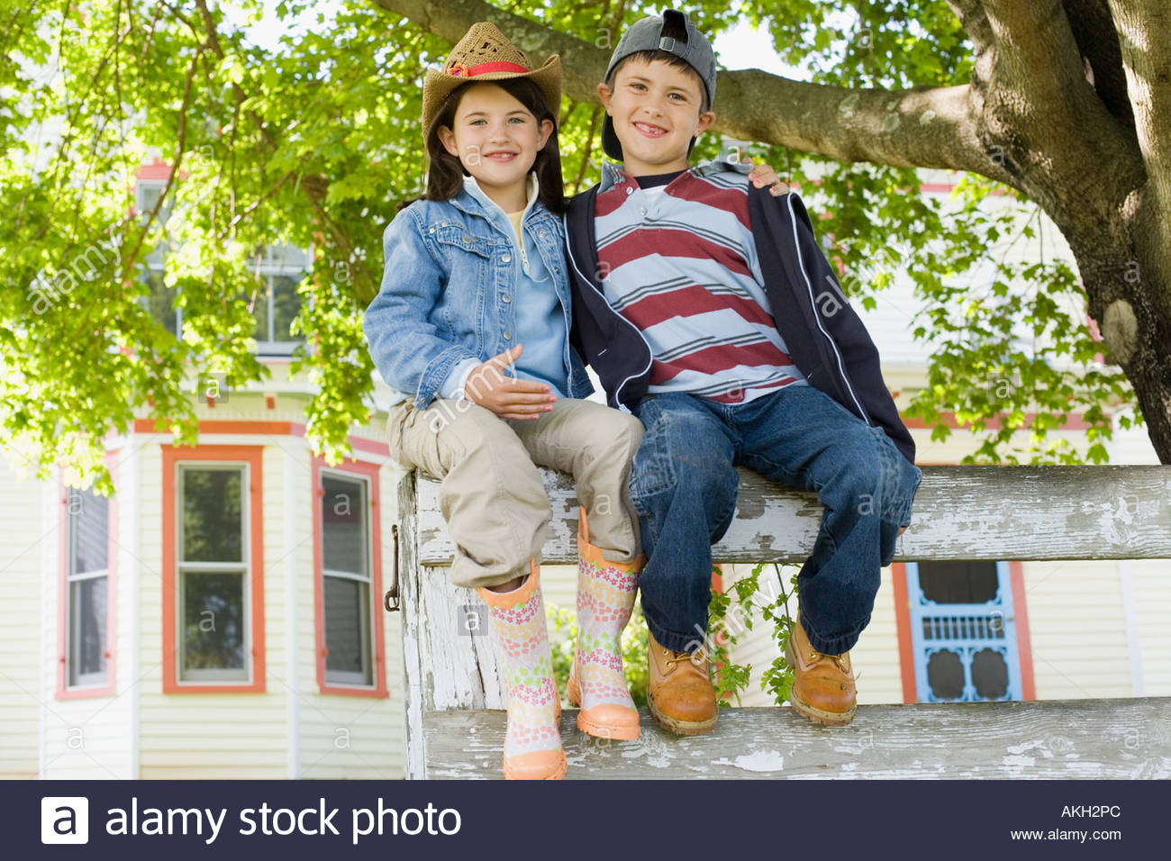 Boy and girl sitting on wooden fence in front of house - Stock Image