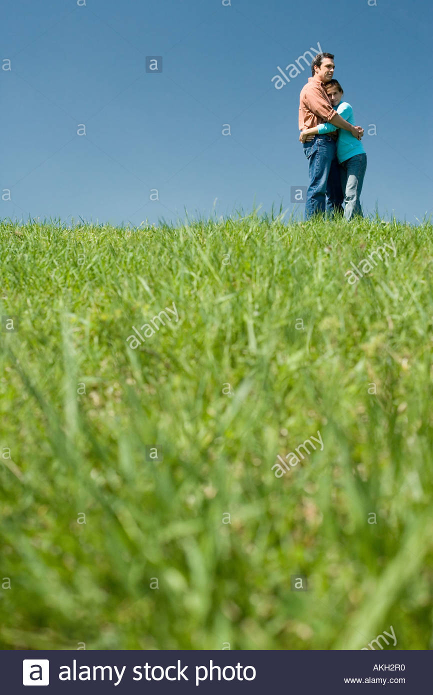 Couple hugging on field - Stock Image