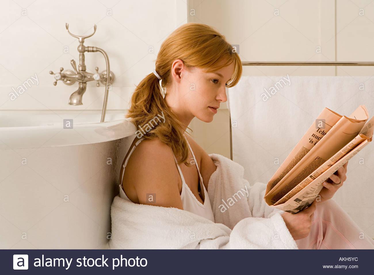 Woman reading newspaper in bathroom - Stock Image