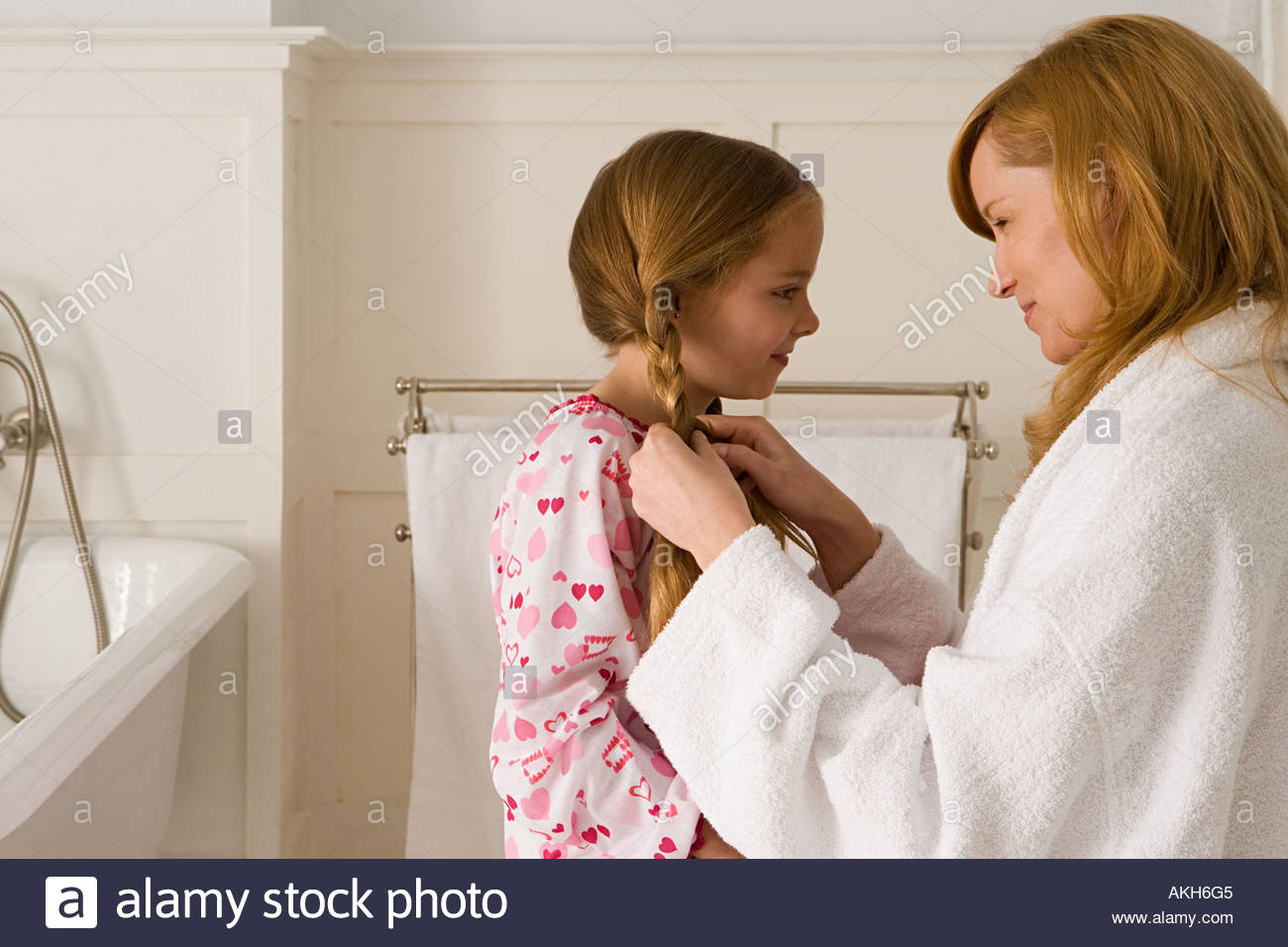 Mother plaiting daughter's hair - Stock Image