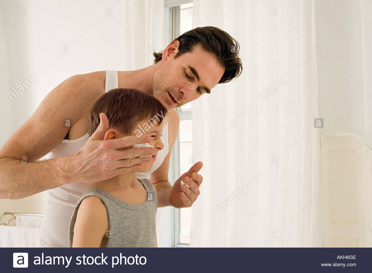 Father putting shaving cream on son - Stock Image