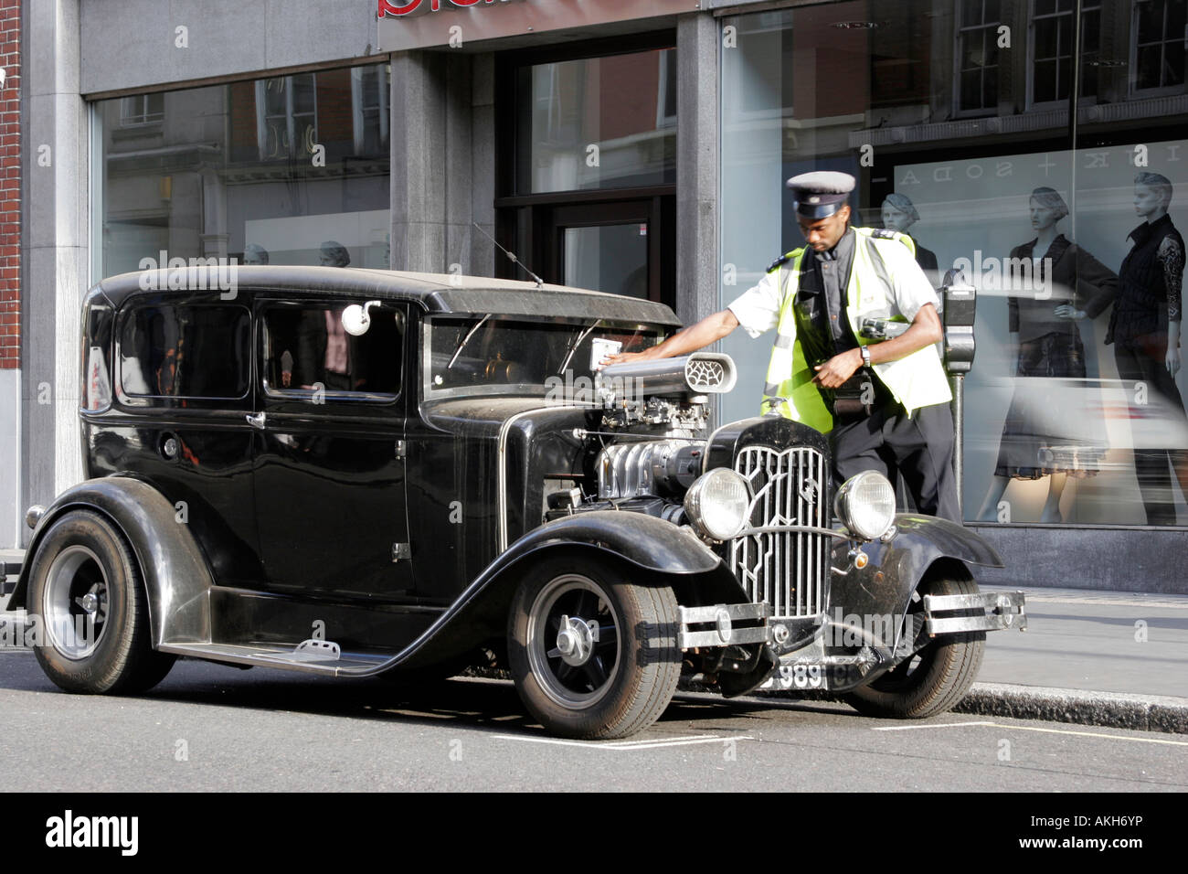 Traffic warden giving a custom car a parking ticket in Central London - Stock Image