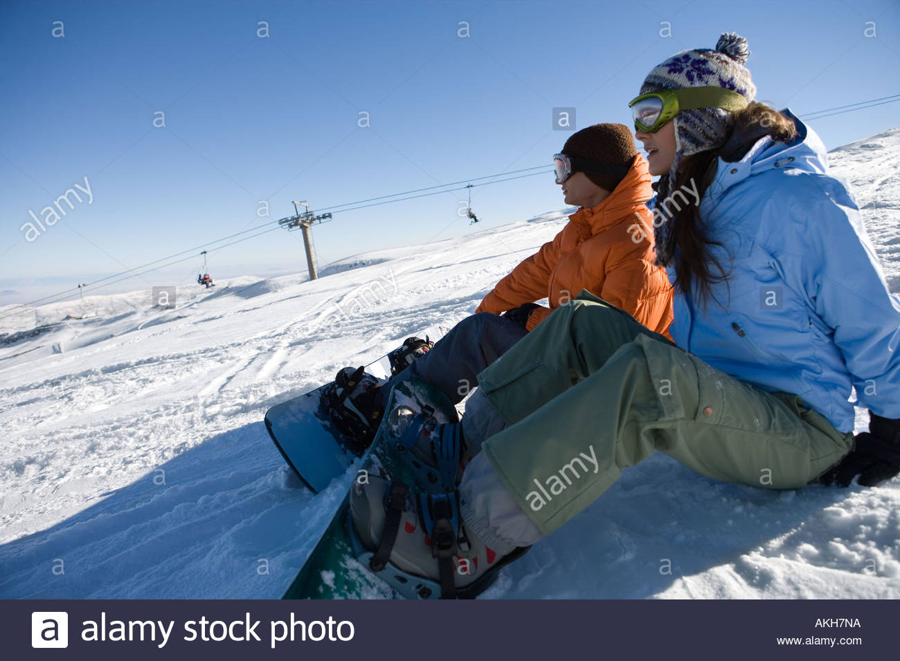 Snowboarders sitting on slope Stock Photo