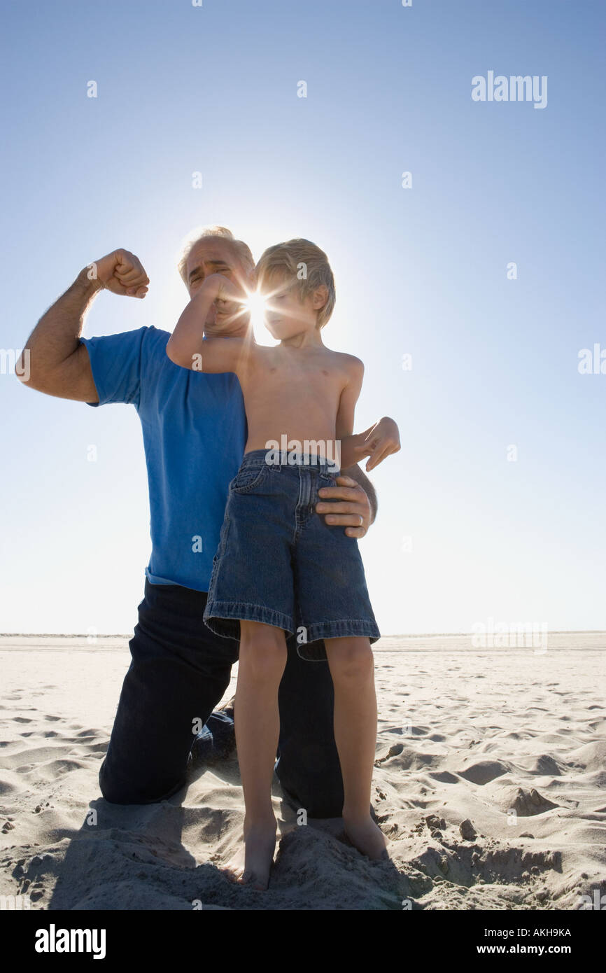 Grandfather and son flexing biceps on beach - Stock Image