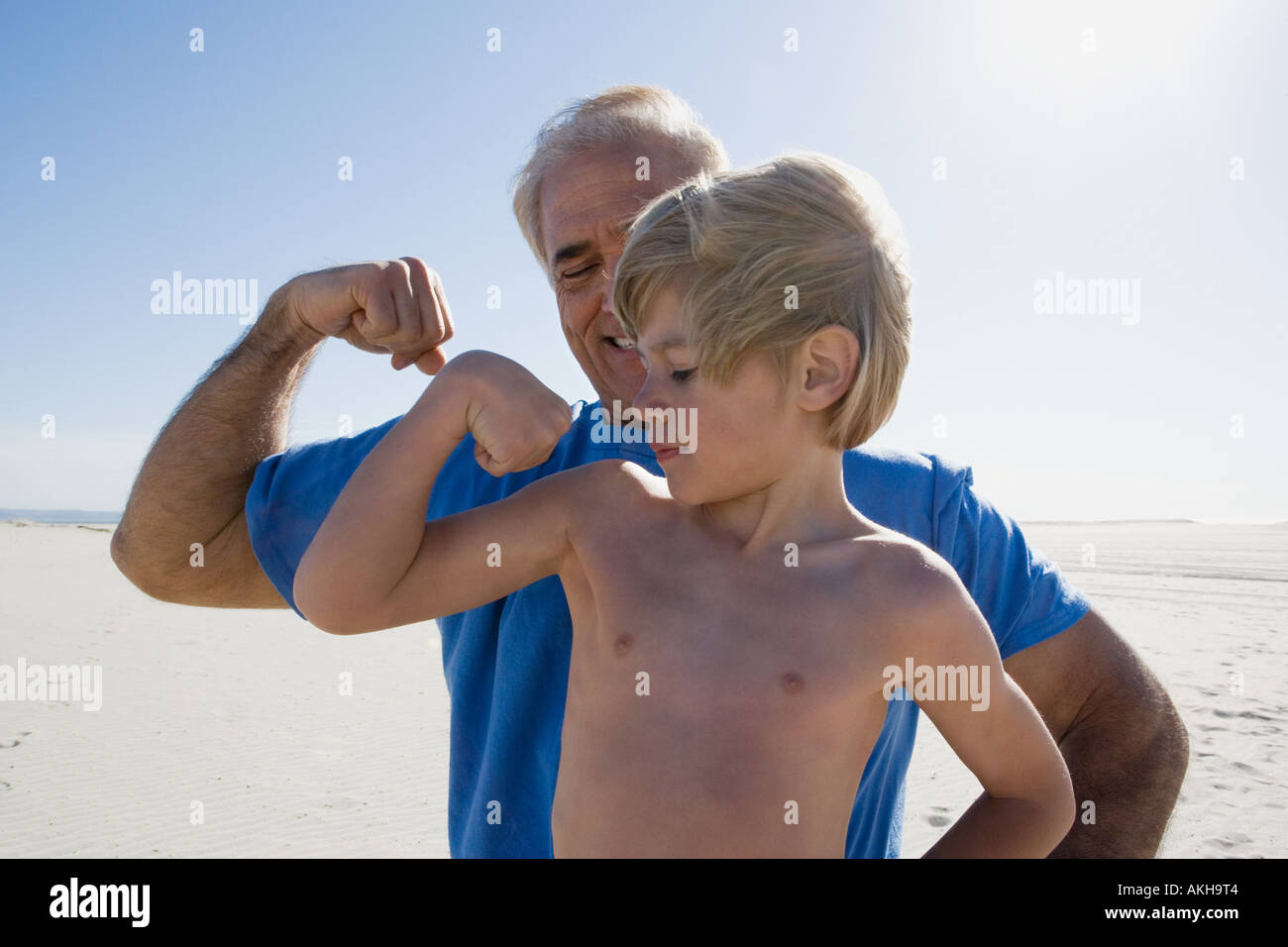 Grandfather and grandson flexing biceps on beach - Stock Image