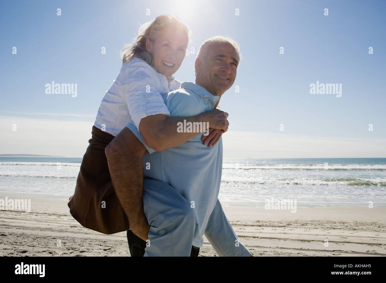 Senior man carrying woman on back - Stock Image