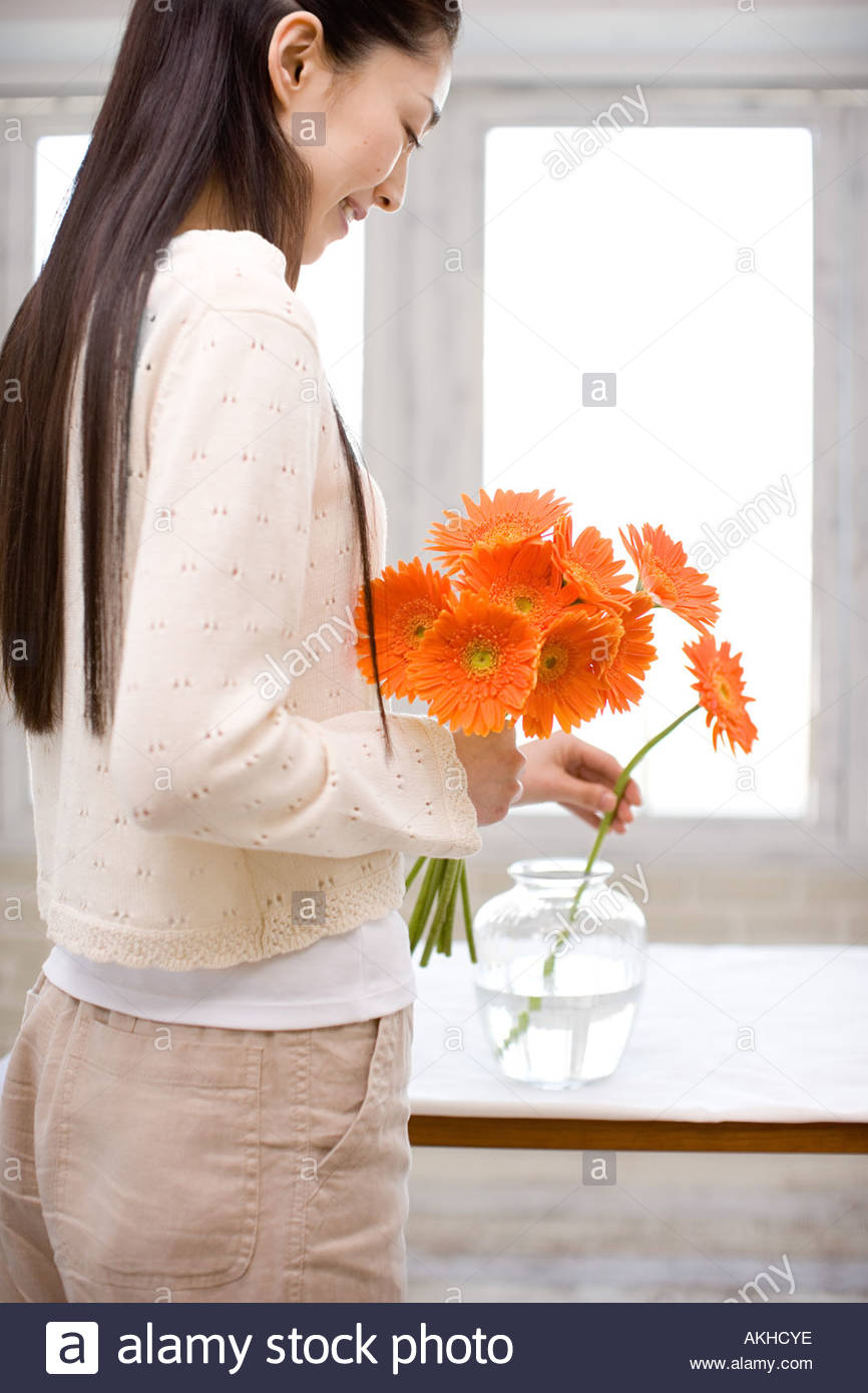 Woman putting flowers in a vase & Woman putting flowers in a vase Stock Photo: 8573629 - Alamy