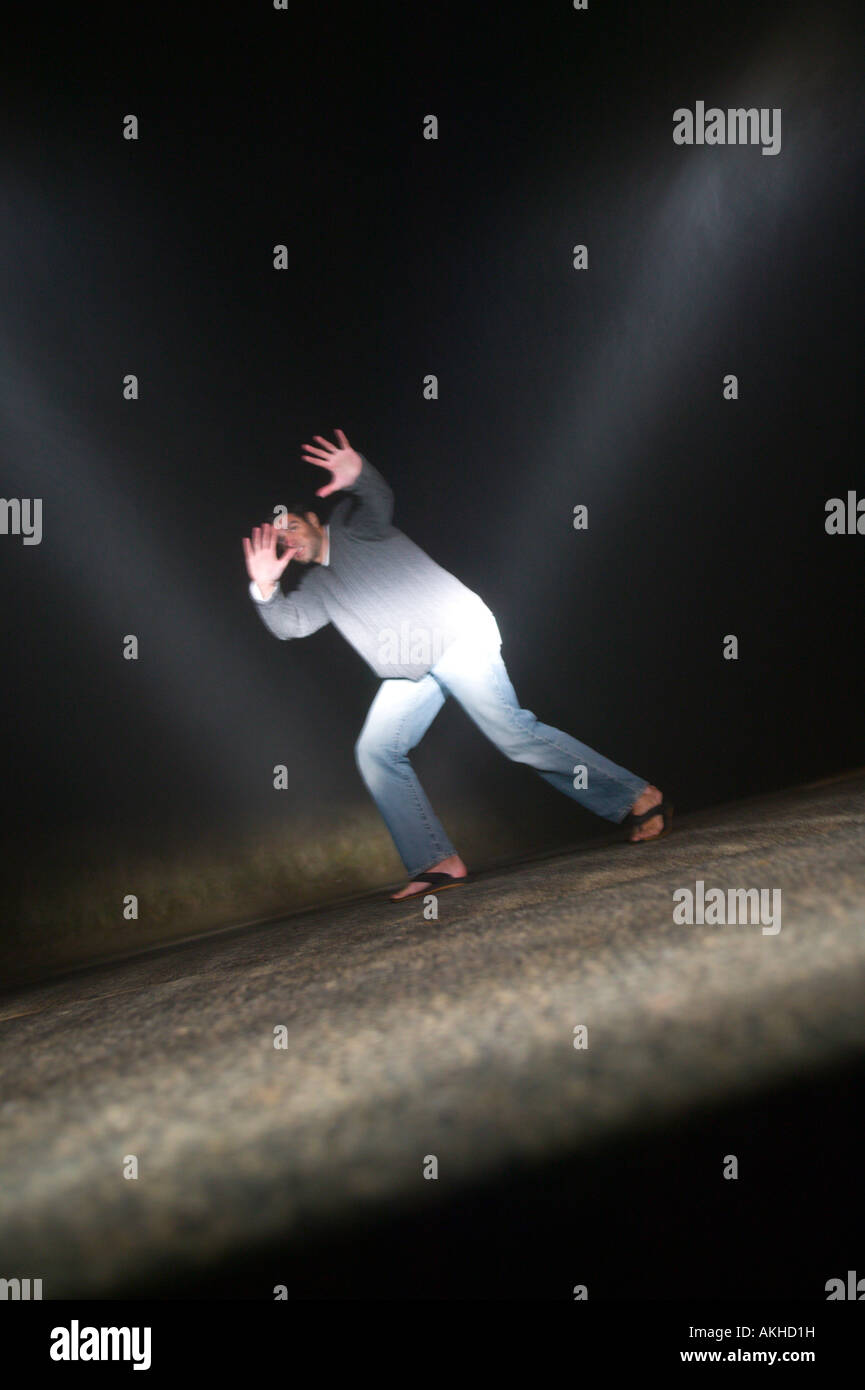 Man in Path of oncoming Car at Night - Stock Image