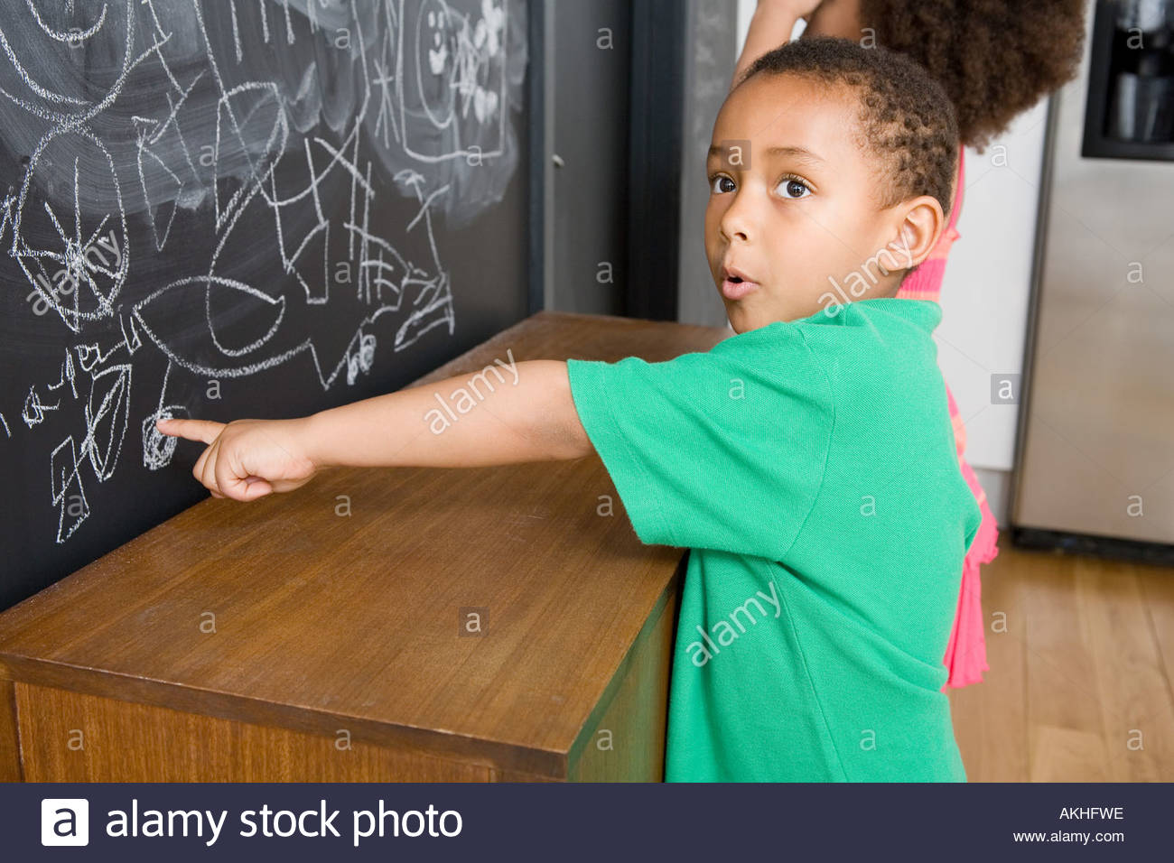 Boy pointing to drawing on blackboard - Stock Image