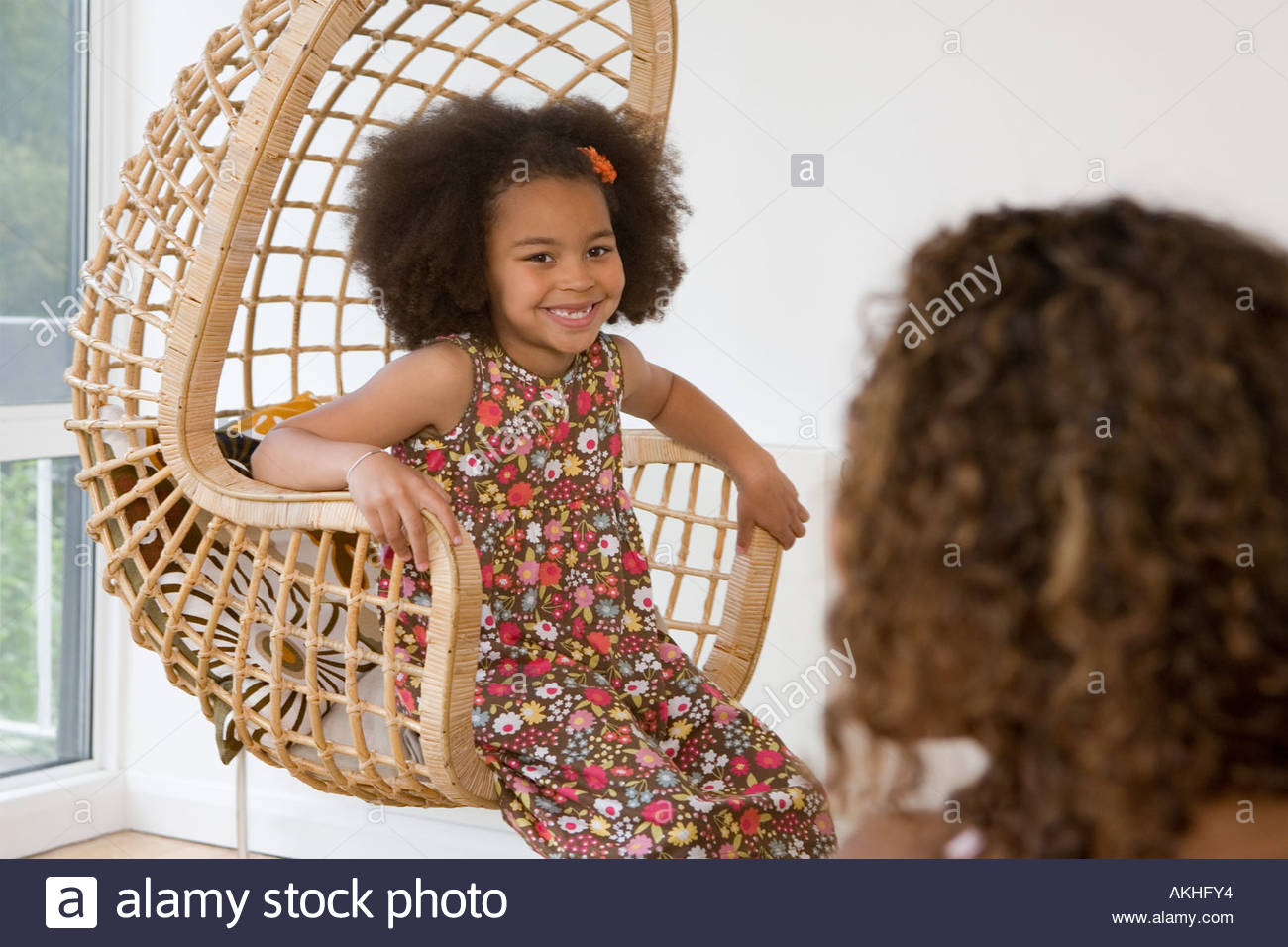 Girl in a wicker chair - Stock Image