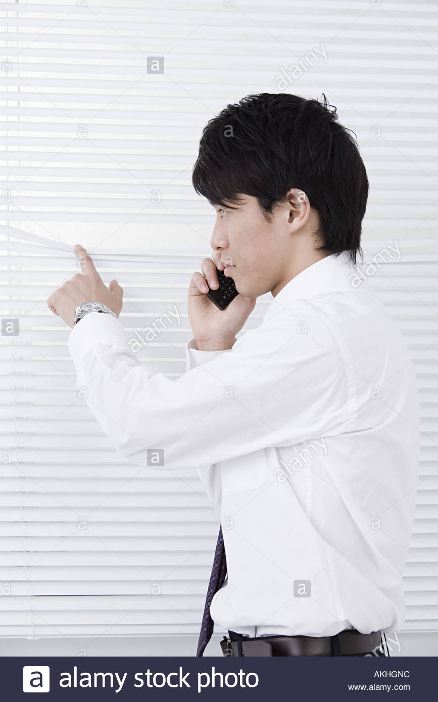 Office worker looking out of blinds - Stock Image