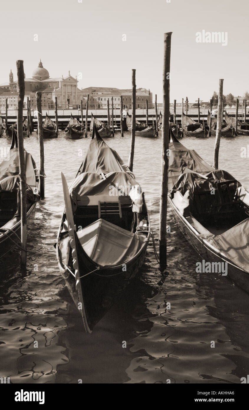 Gondolas tied up at San Marco with San Giorggio Maggiore in the distance Grainy glow effect and monochrome sepia toninig - Stock Image