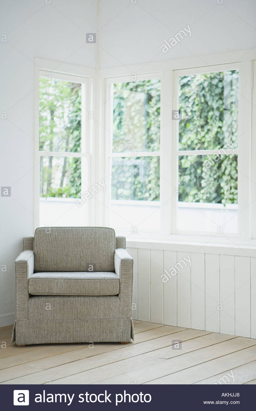 Armchair in the corner of a room - Stock Image