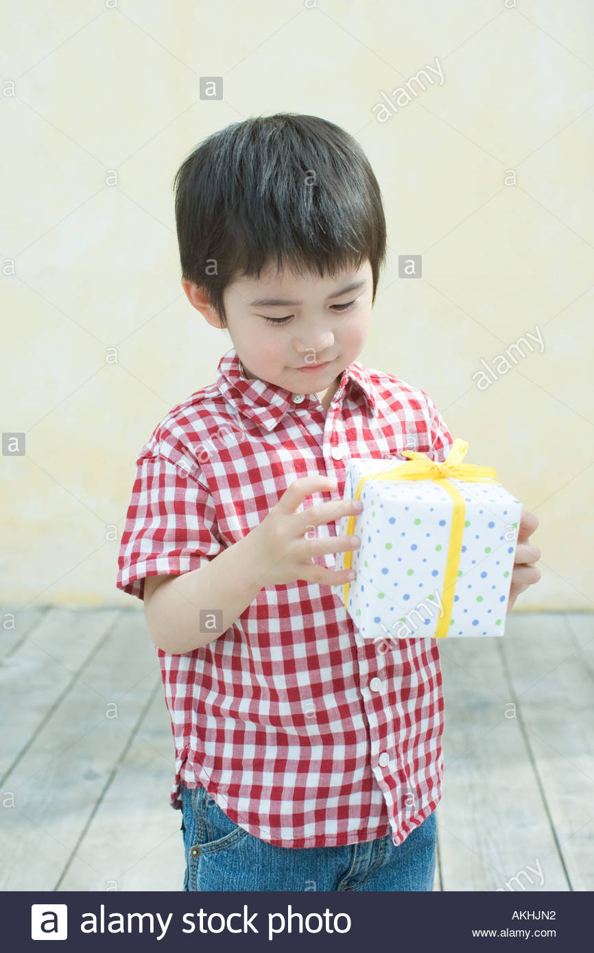 Asian boy holding a gift - Stock Image
