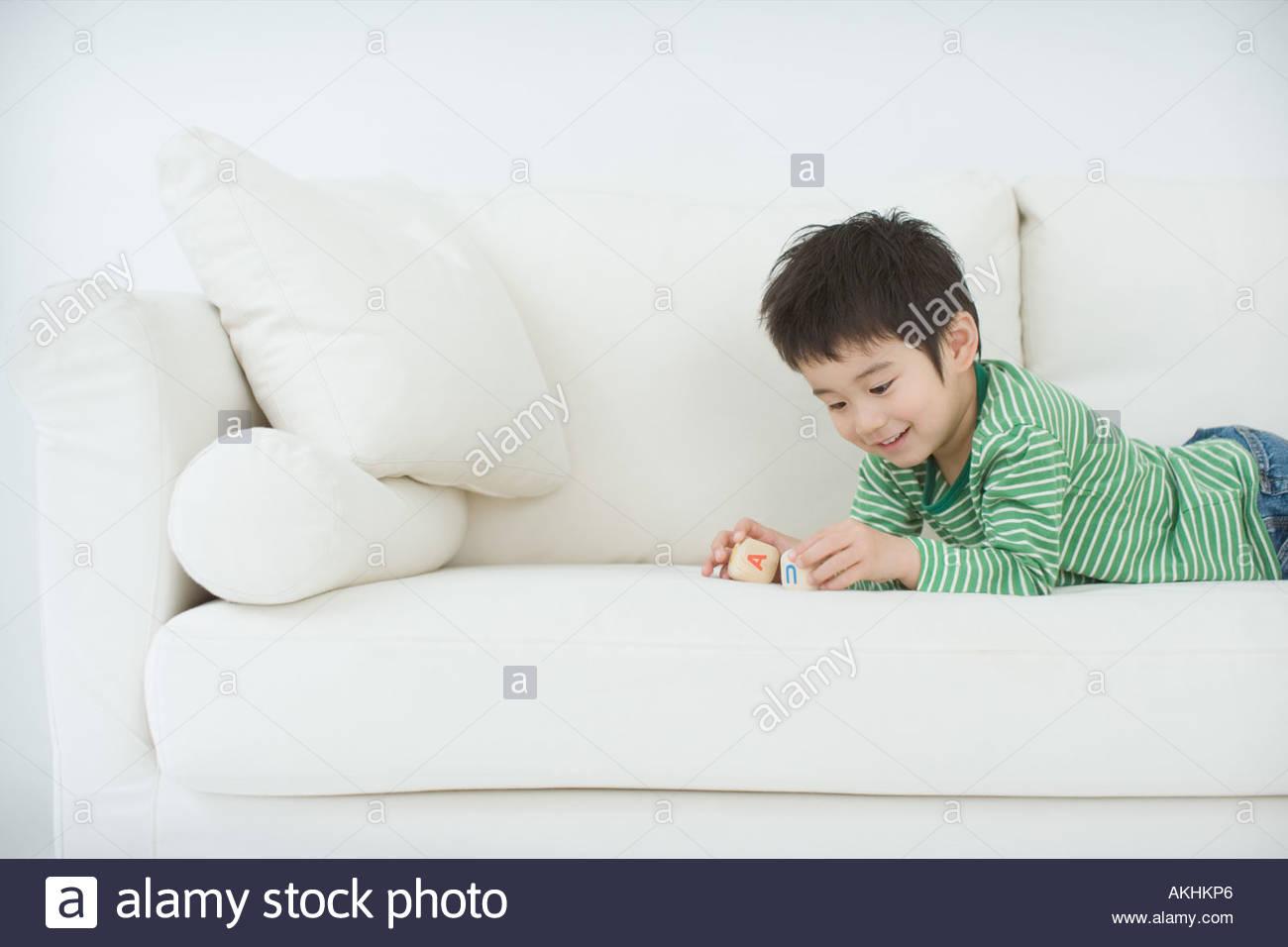 Japanese boy playing on sofa - Stock Image