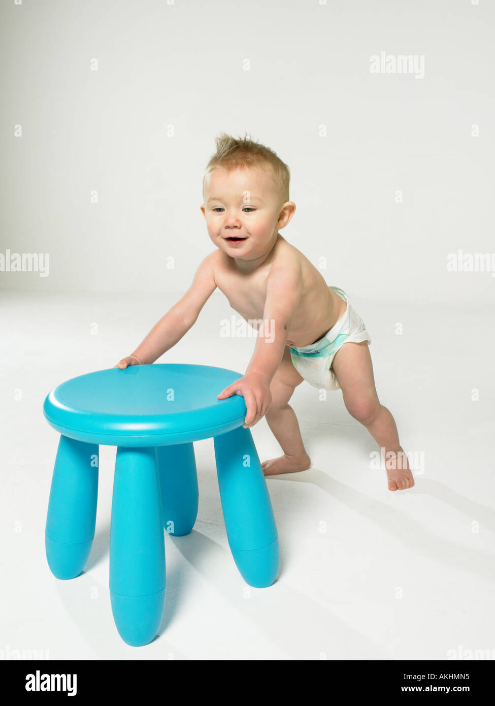 Baby with blue stool - Stock Image