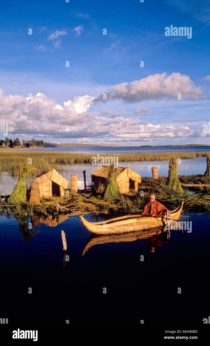 man of uros tribe riding totora reed boat at evening floating island made by totora reed lake titicaca peru bolivia - Stock Image