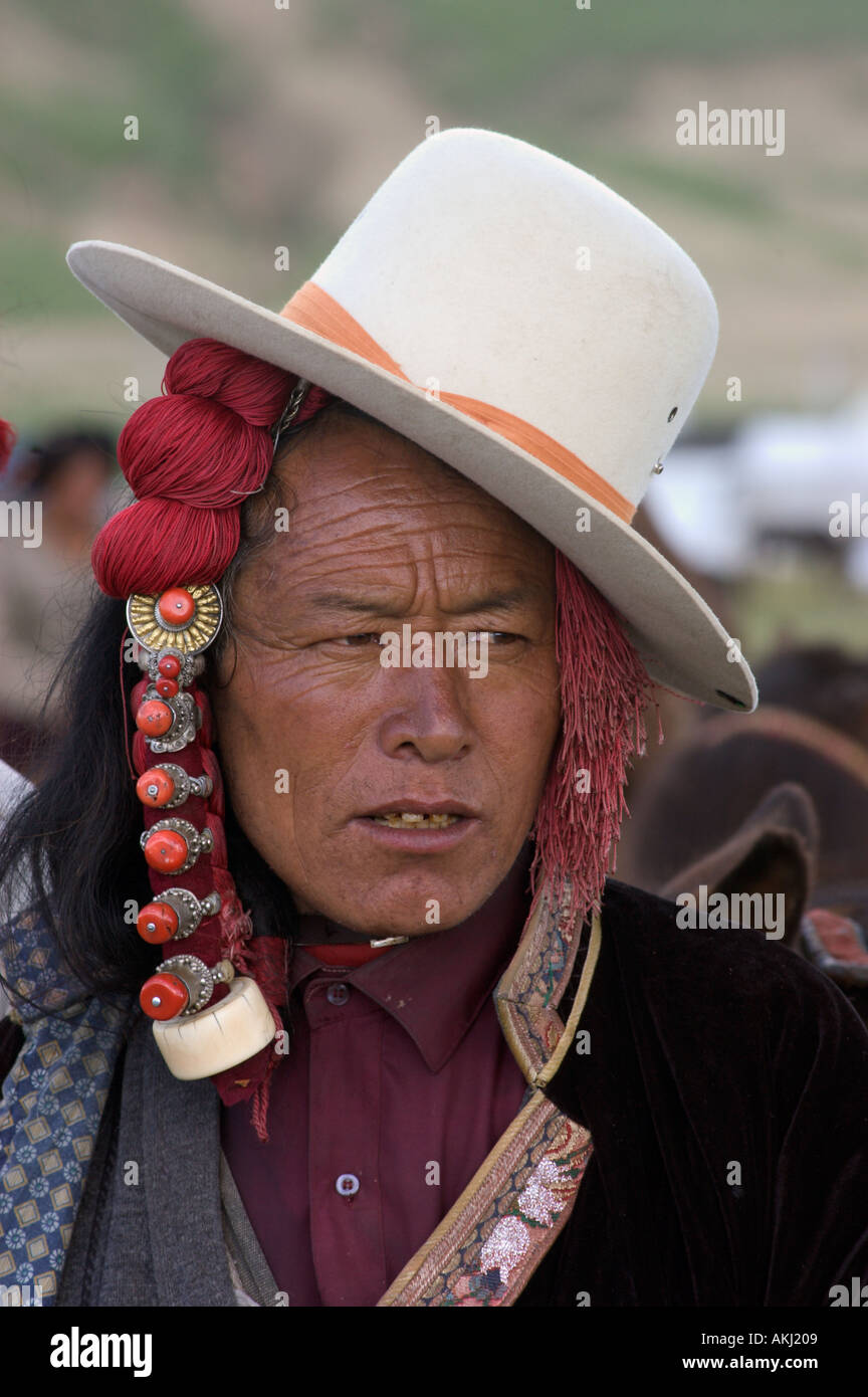 Khampa with jaunty cowboy hat and ivory hair peices at the Litang Horse Festival in Kham Sichuan Province China Tibet  - Stock Image