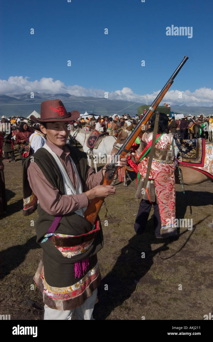 Khampa man with rifle used in competition at at the Litang Horse Festival Kham Sichuan Province China Tibet  - Stock Image
