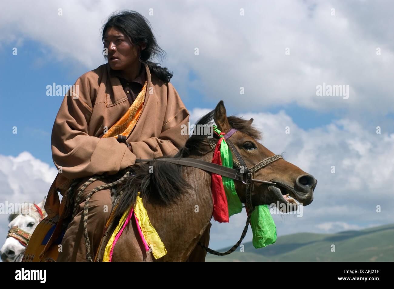 Khampas the warrior horseman of old Tibet compete at the Litang Horse Festival Kham Sichuan Province China Tibet  - Stock Image