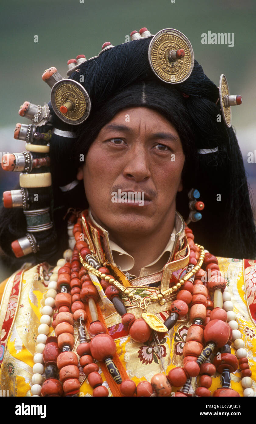 Male Khampa wears coral zee stones gold hair ornaments at the Litang Horse Festival Sichuan Province China Tibet Stock Photo
