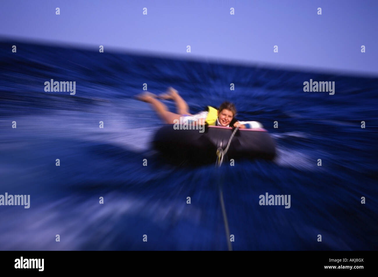 A young teen tubing - Stock Image