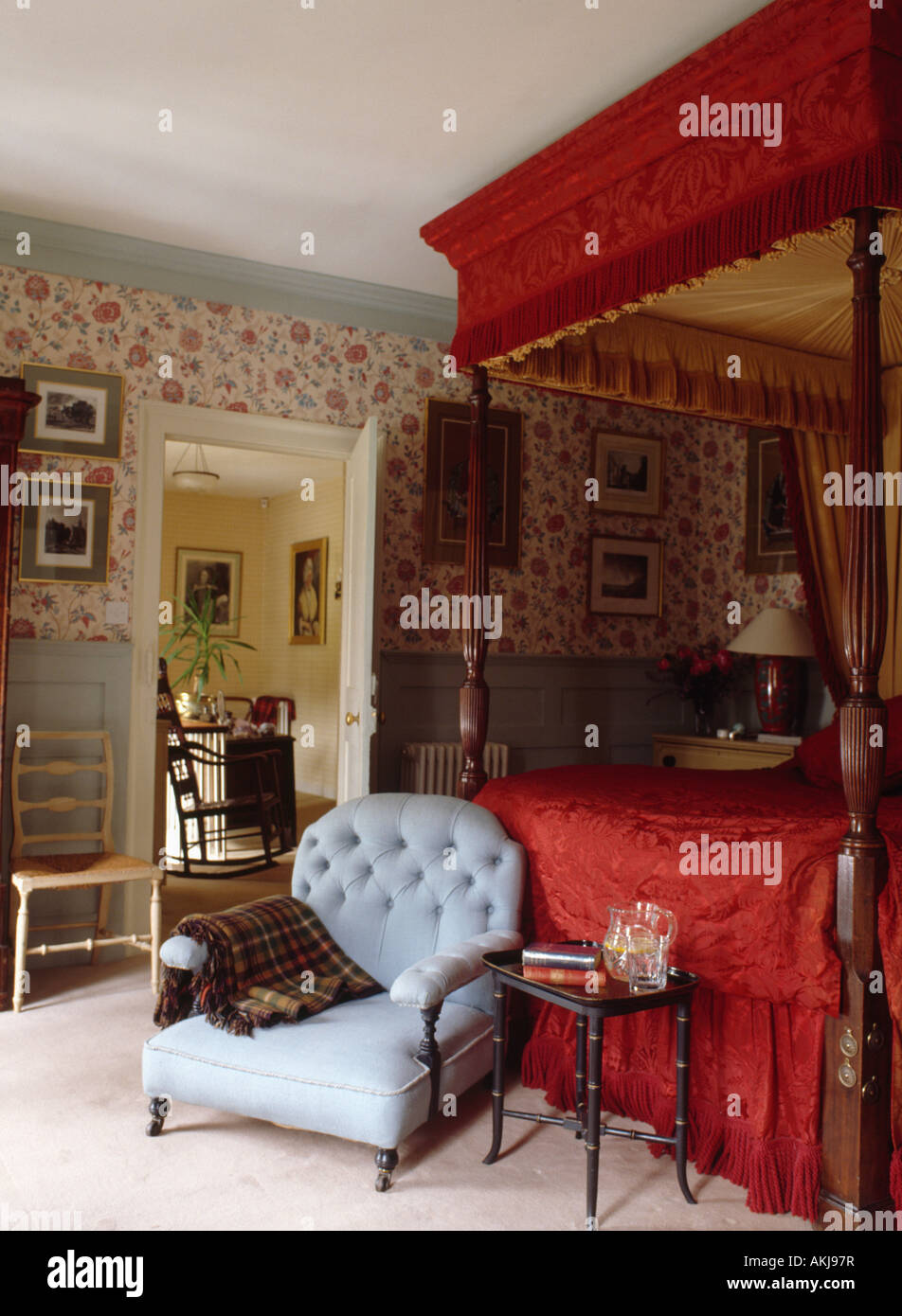 red silk canopy and cover on antique four poster bed in country bedroom with pastel blue armchair and floral wallpaper