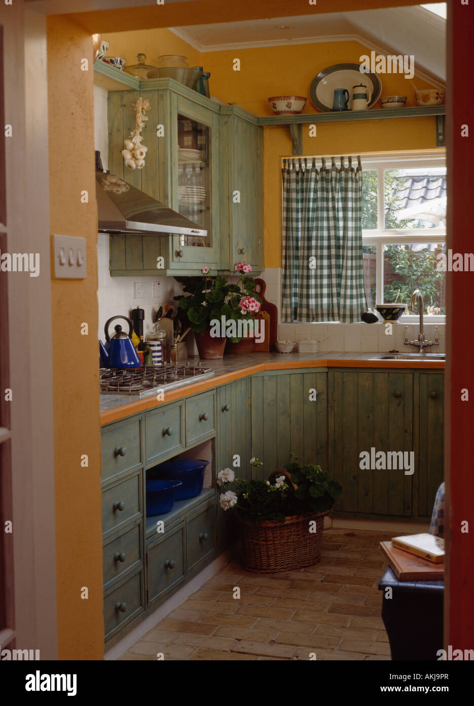 Pastel Green Cupboards And Units In Small Pale Orange Kitchen Extension  With Green Checked Curtains