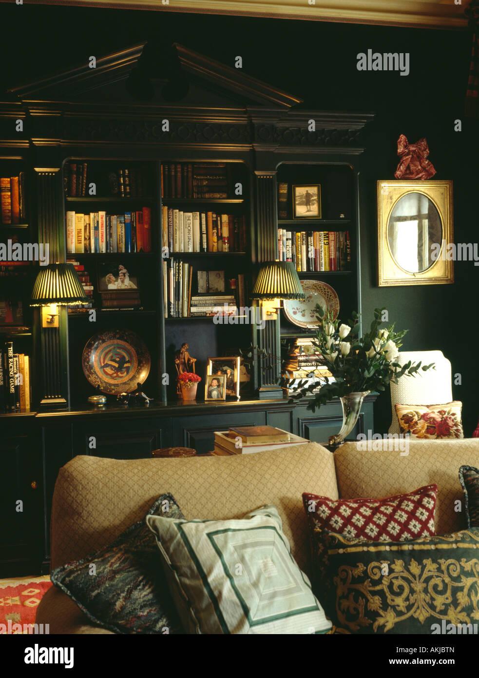 Dark Green Living Room.Lighted Lamps On Fitted Bookshelves In Dark Green Living
