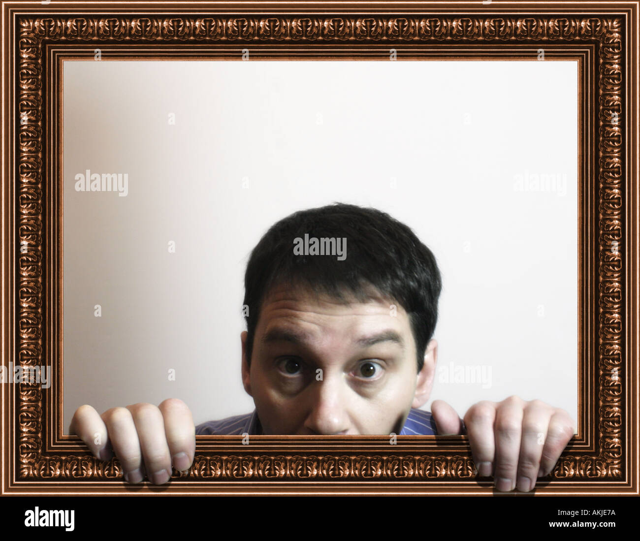 Composite with man hiding from within a picture frame - Stock Image