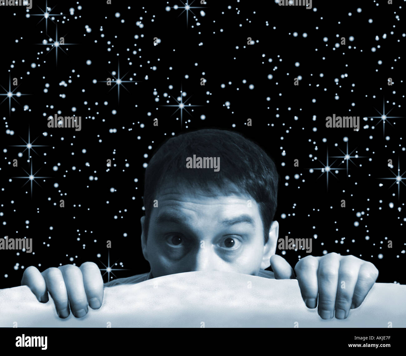 Composite with man in cold outside with star strewn sky - Stock Image