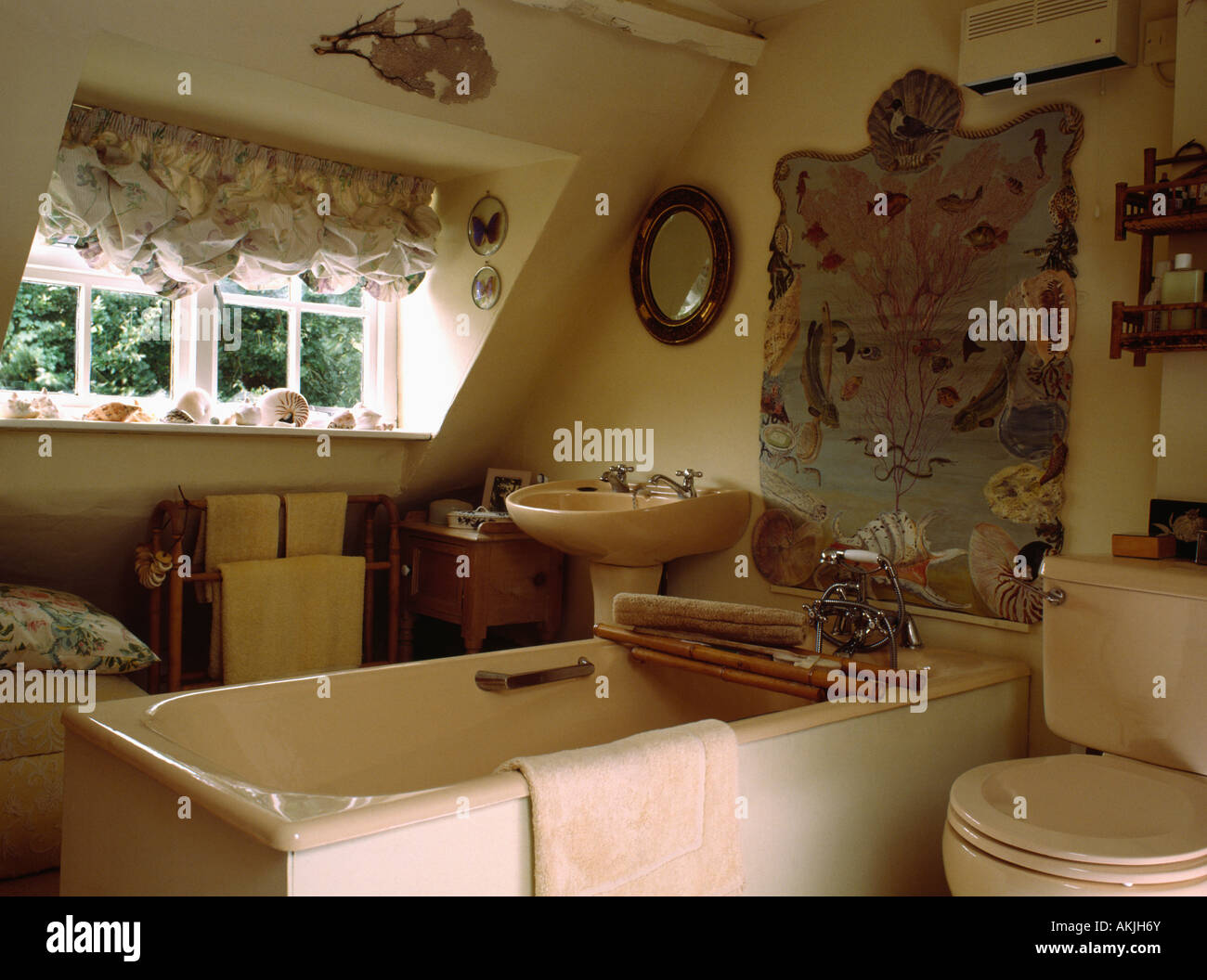 Pink bath and toilet in attic bathroom with festoon blinds at the ...