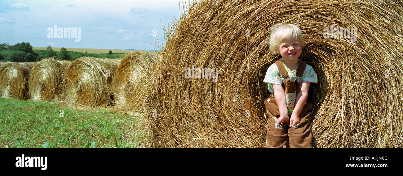 Two years old girl sitting on a bale of hay. Altai. Siberia. Russia - Stock Image