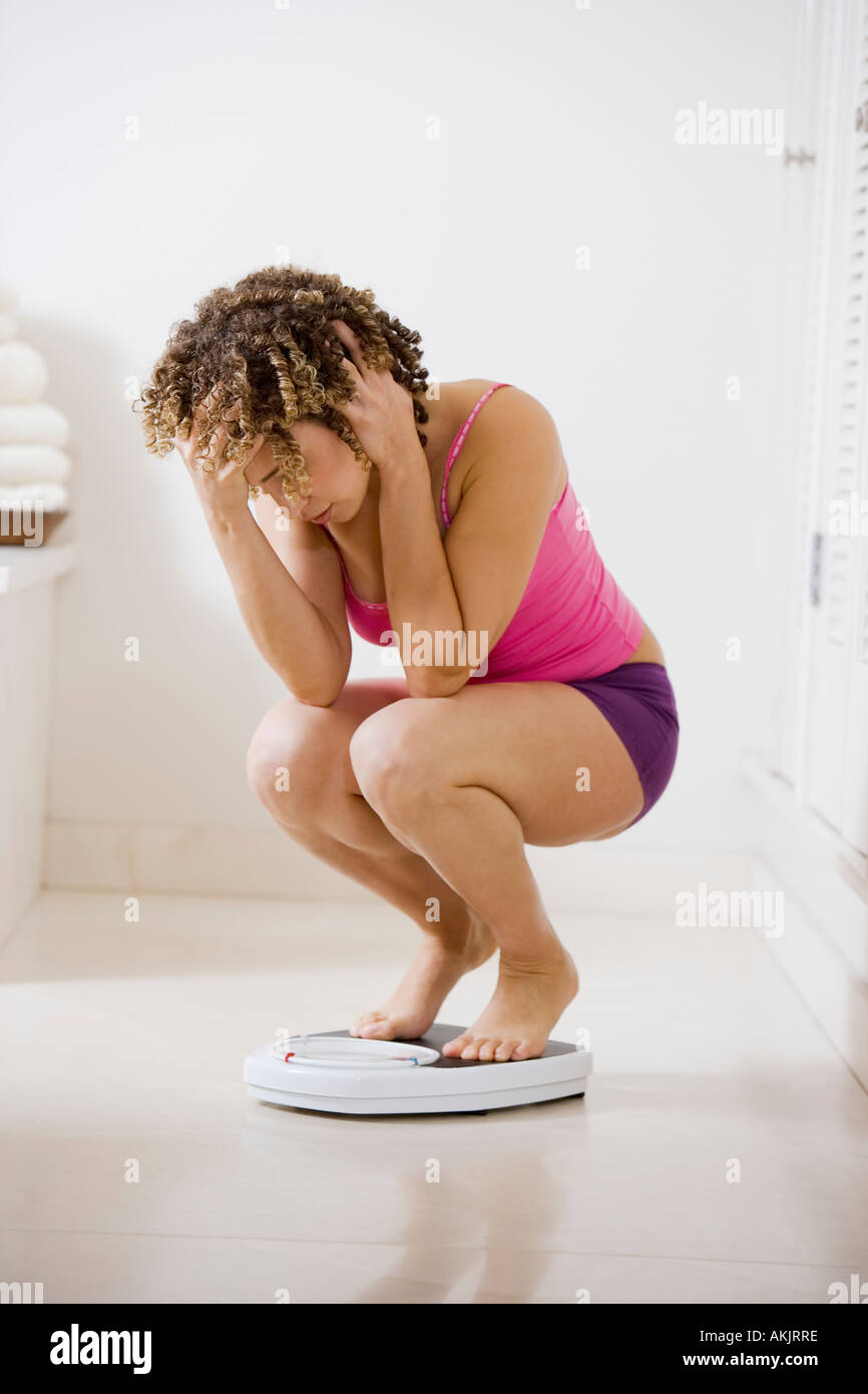 Stressed woman crouching on bathroom scale - Stock Image