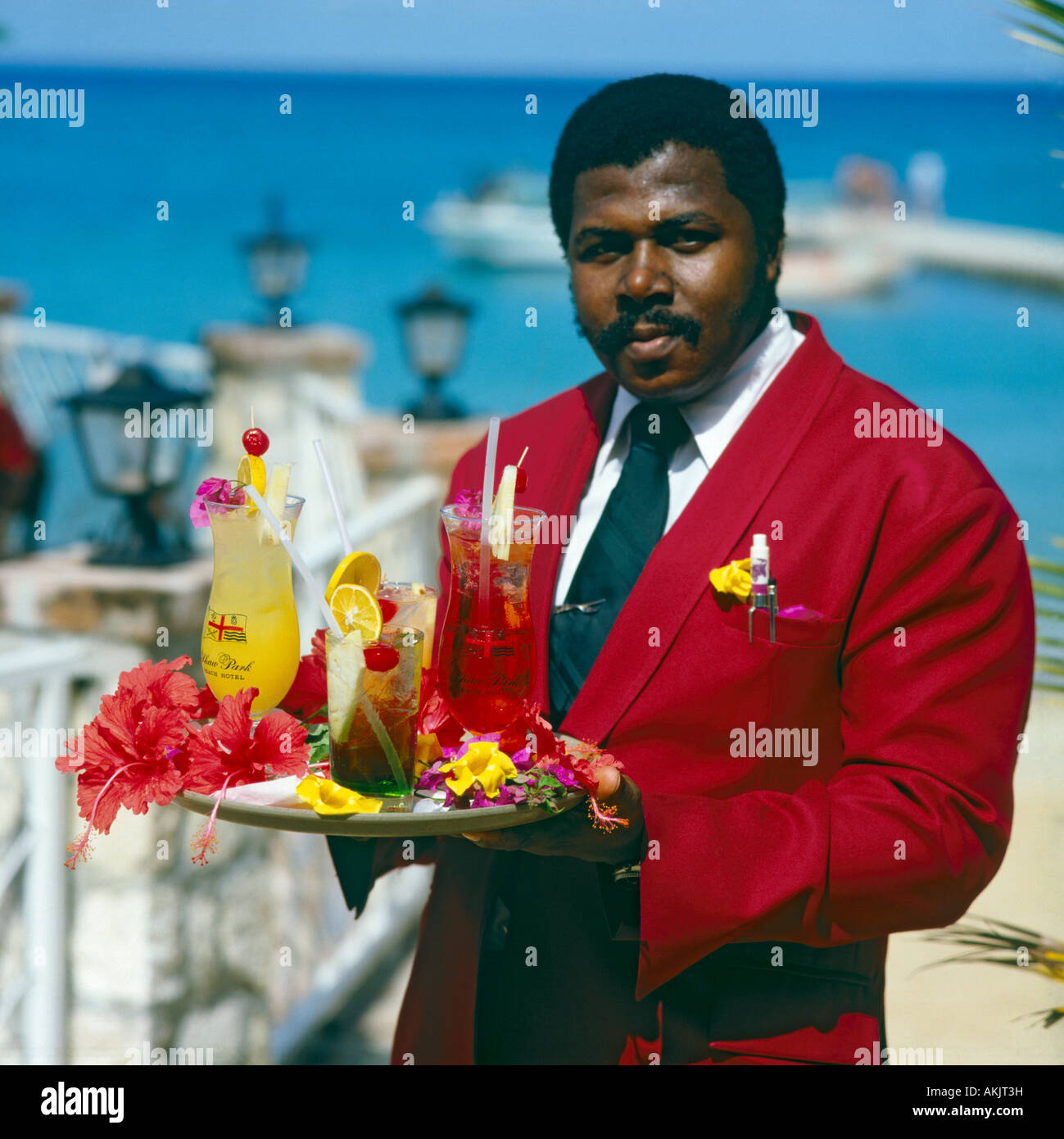 a40af58f4afee Local male waiter in red coat white shirt and tie holding tray of colourful  red   yellow tropical drinks at Ocho Rios in Jamaica