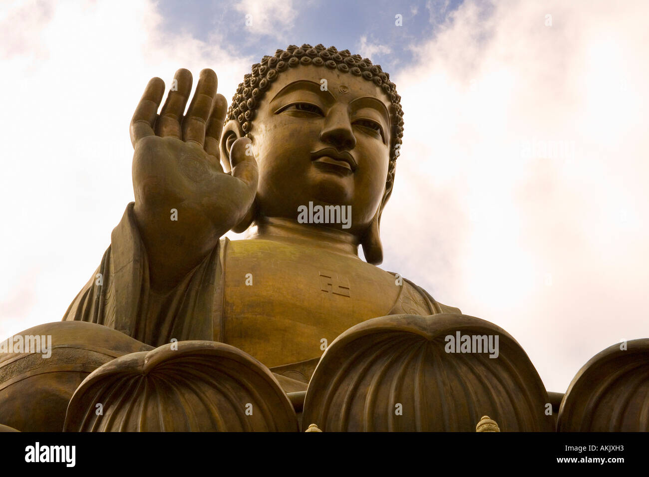 Massive statue of seated Buddha with clouds Stock Photo