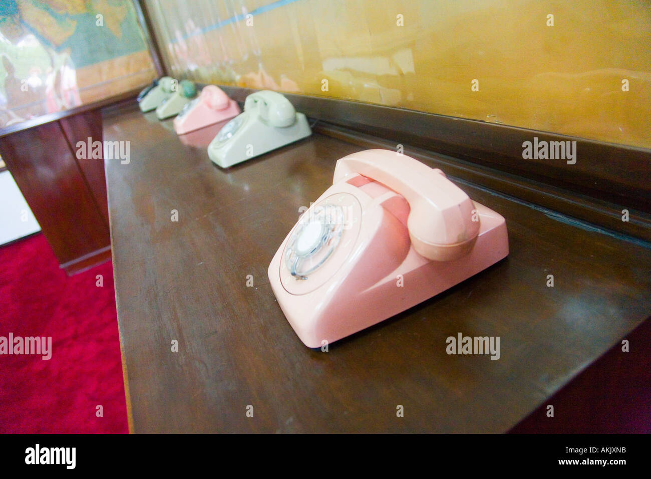 Pastel colored telephones on counter with maps - Stock Image