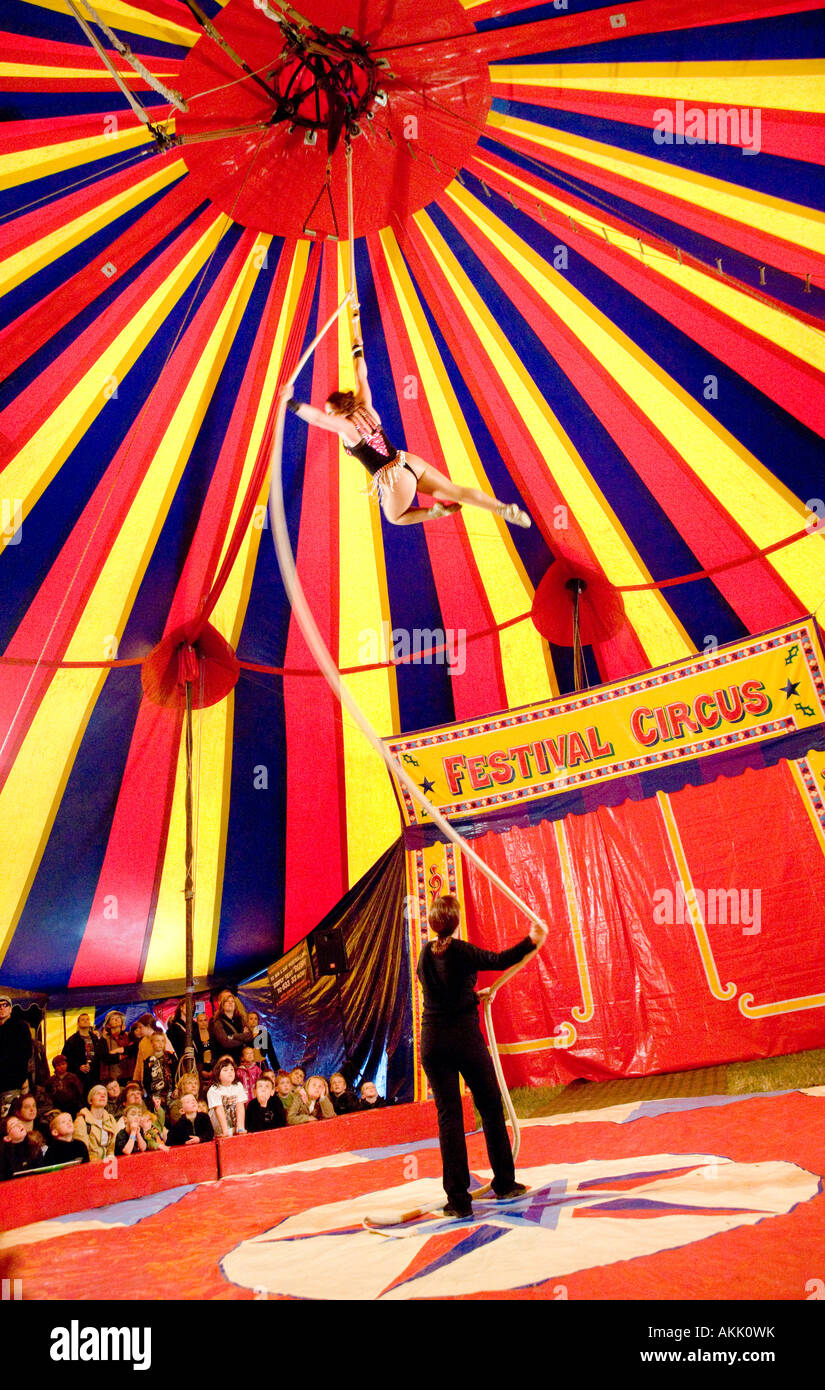 Festival Circus girl swinging on a rope high up in the air under a big top circus tent Wickerman Music Festival - Stock Image