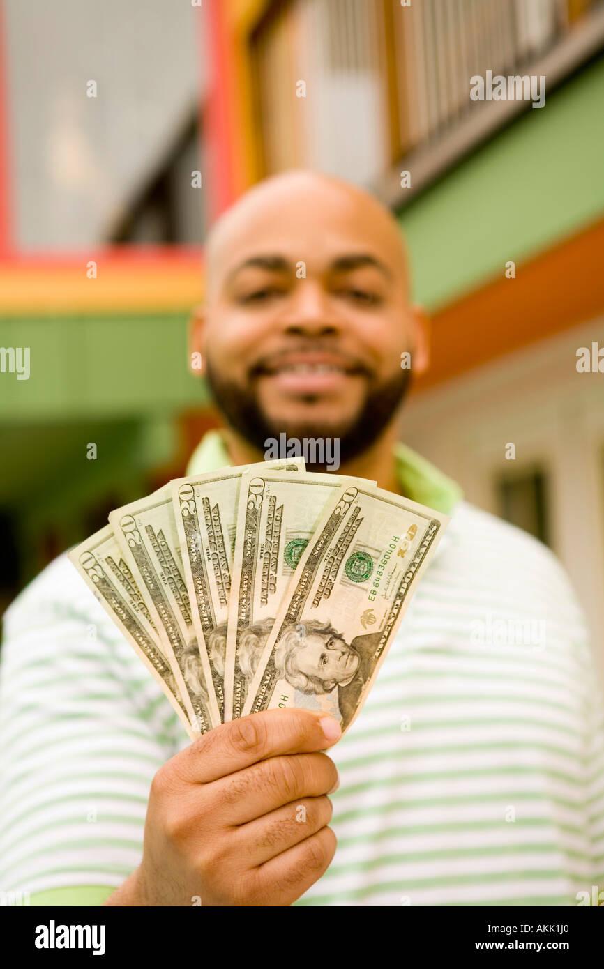 Man holding twenty dollar bills Stock Photo