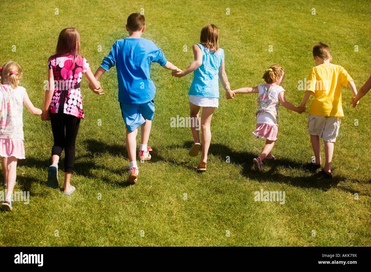 Rear view of children running - Stock Image