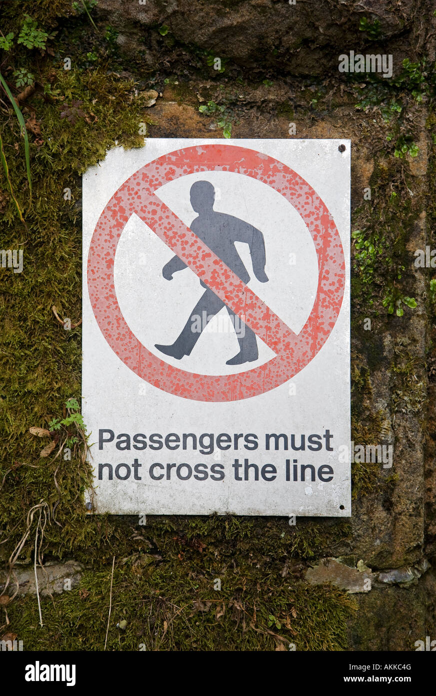 Safety sign on railway platform 'Passengers must not cross the line' - Stock Image