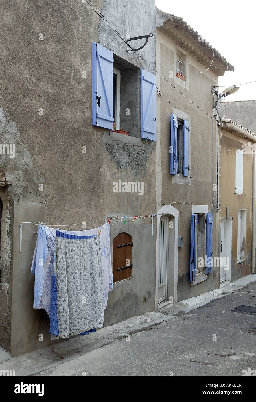 a traditional european village street scence with pretty blue window shutters and washing hanging to dry in the - Stock Image