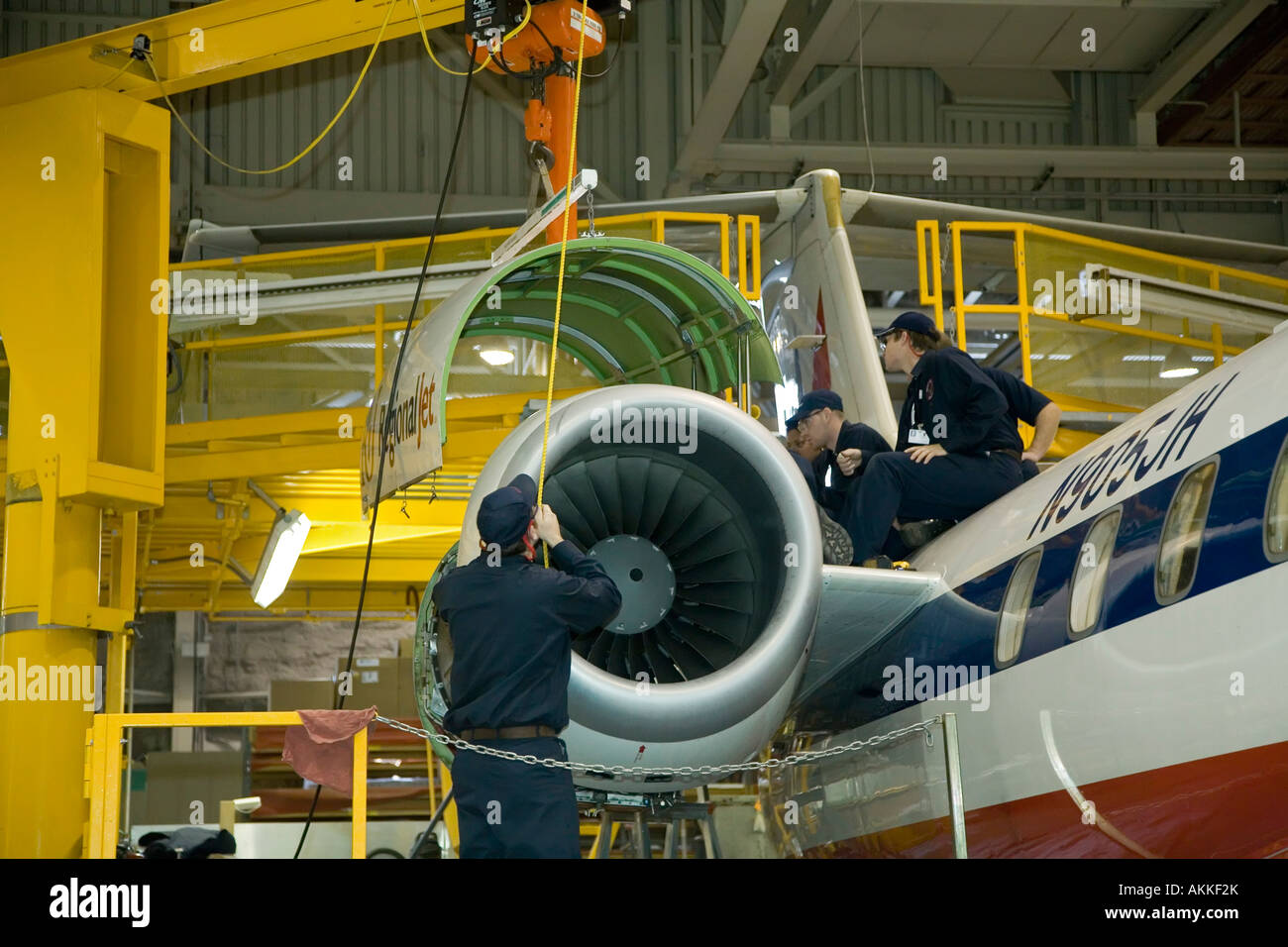 Workers do heavy maintenance on American Eagle Embraer jet airplanes at Sawyer International Airport - Stock Image