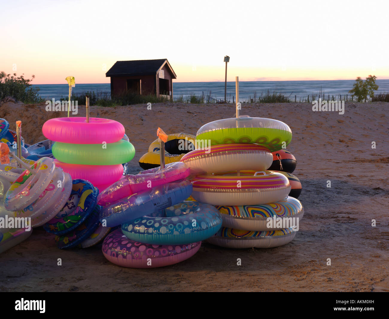 Canada Ontario Sauble Beach beach floatation devices at a beach stand illuminated at dusk with beach in background - Stock Image