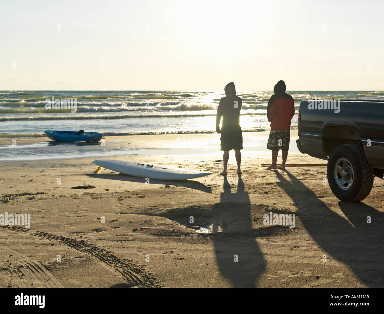 Canada Ontario Sauble Beach two male friends early twenties at beach with surf board and kayak looking out towards - Stock Image