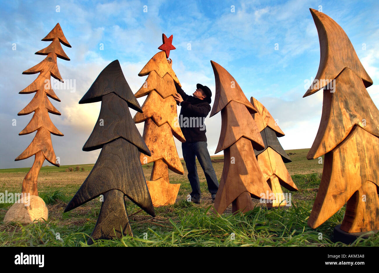 Artist johnny woodford with his surreal wooden christmas trees