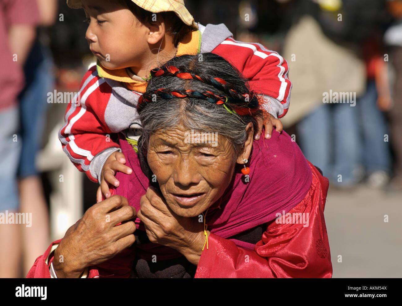 Elderly Tibetan woman carrying her grandchild on her back Lhasa Tibet - Stock Image
