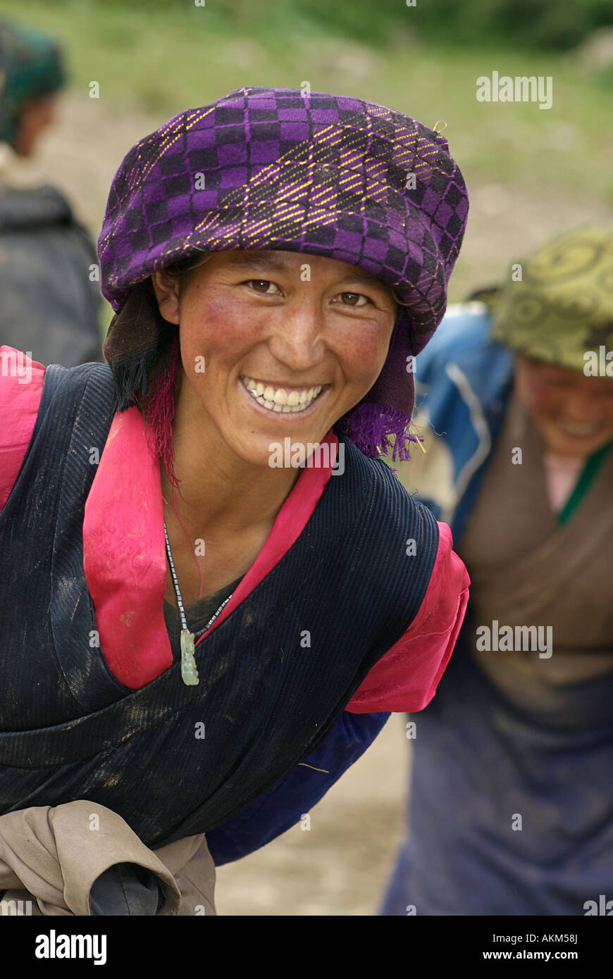 Friendly Tibetan woman working carrying a load on her back Tibet - Stock Image