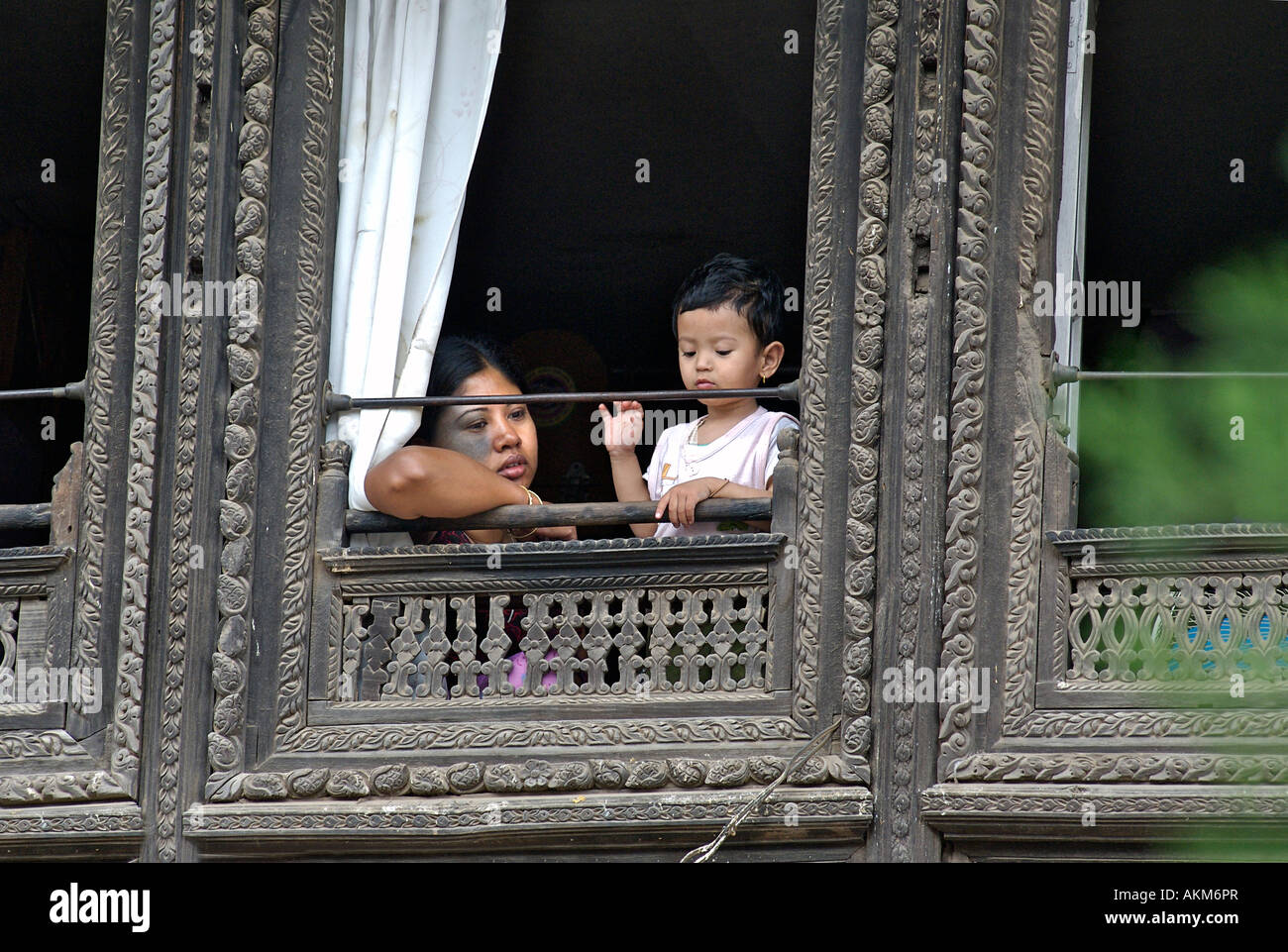 Mother and child looking out of an ornately carved window in the Patan area of Kathmandu Nepal - Stock Image