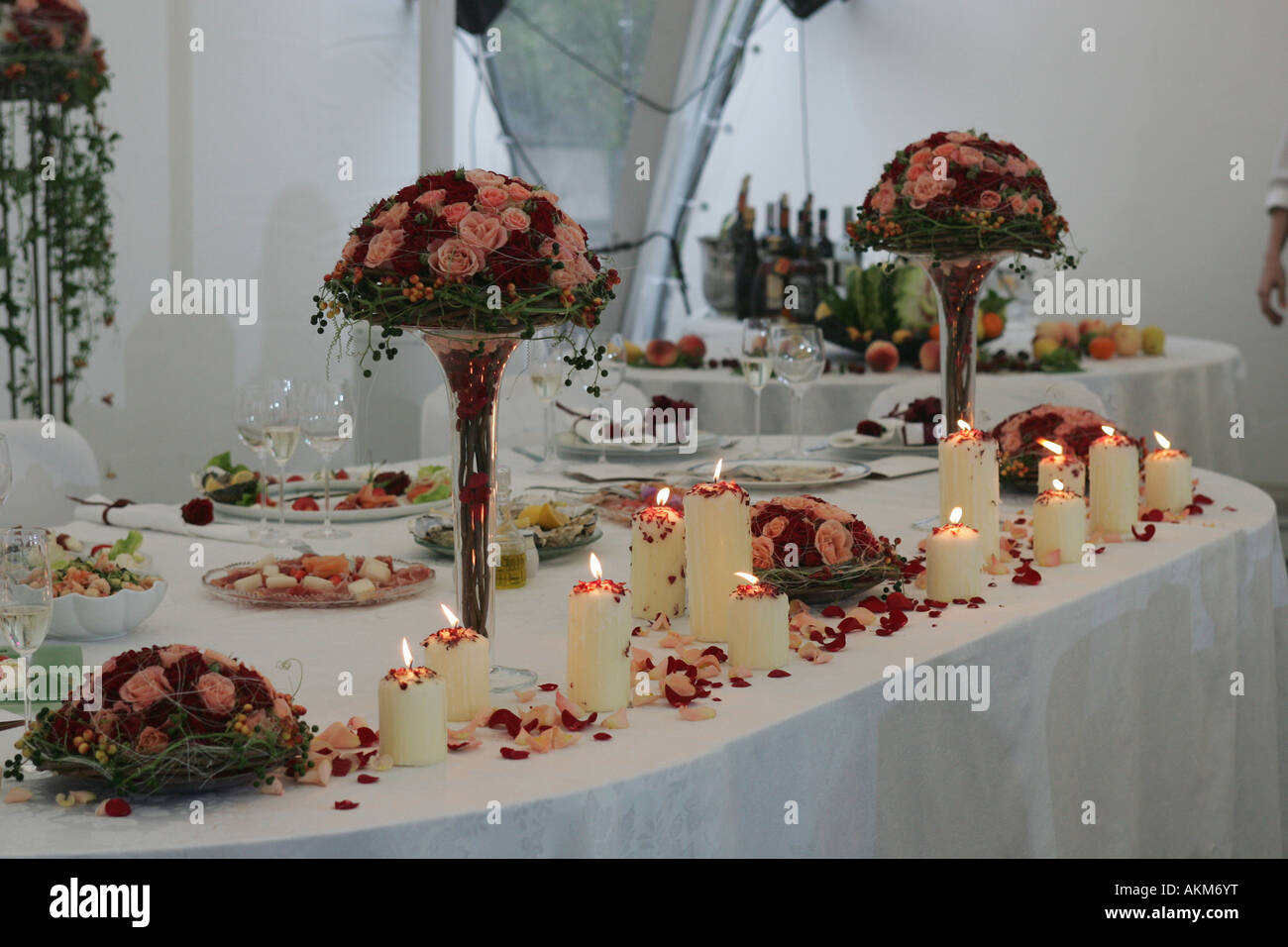 Some burning candles burning on the high table at a wedding reception. This is the table used by the bride and groom. - Stock Image